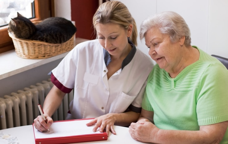 caregiver fills out form with elderly woman
