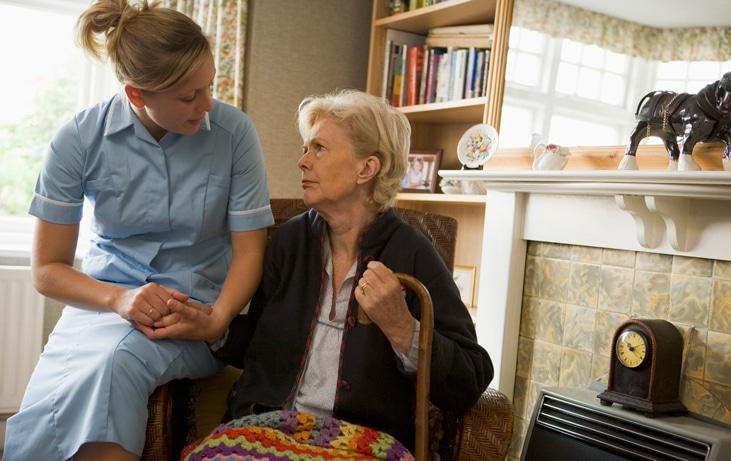 volunteer sits with elderly woman