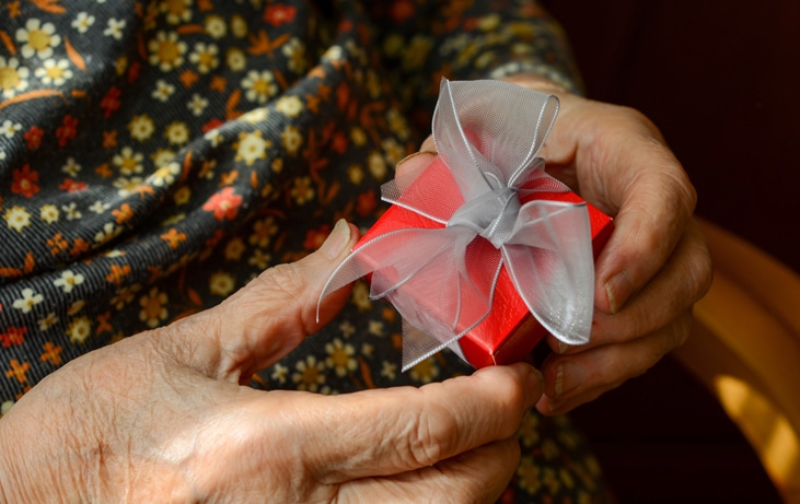 hands of senior holding small gift