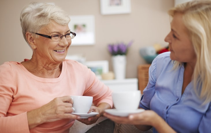 caregiver drinks tea with elderly woman