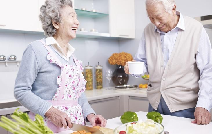 senior couple preparing food in kitchen