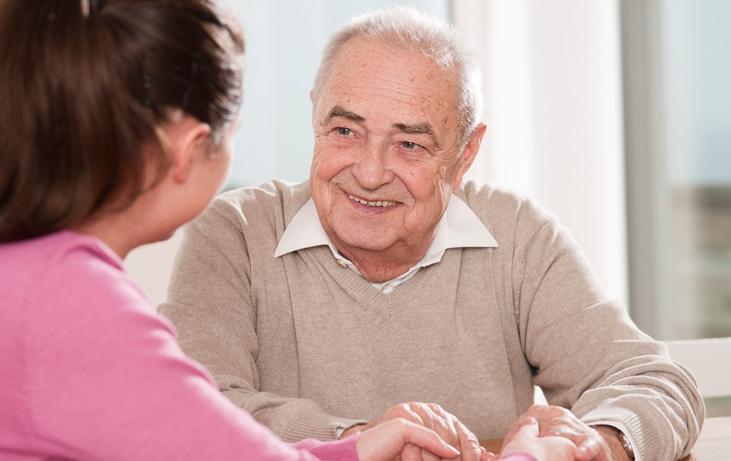 elderly man talking with caregiver