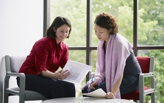 Two-women-meeting--explaining-paperwork