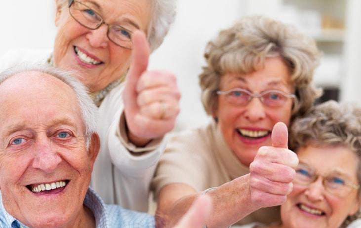group of seniors smiling and giving thumbs up