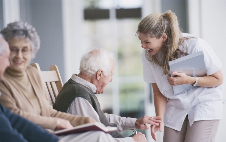 female doctor happily speaks with elderly man