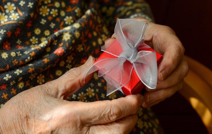 senior holding a gift