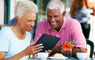 senior couple using tablet at restaurant