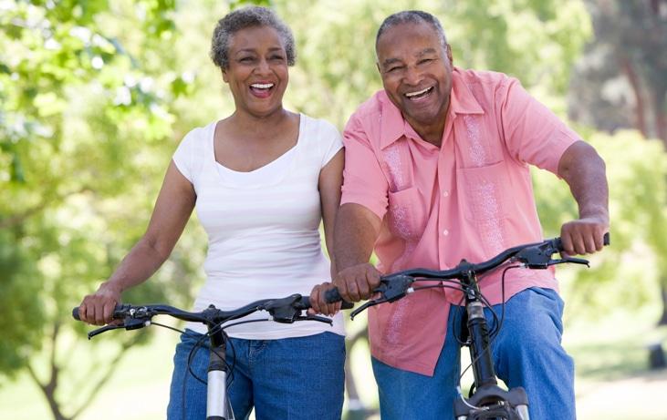 senior couple riding bikes outside